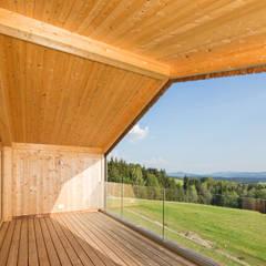 Balcón de estilo  por BRUNTHALER Massivholzhaus,