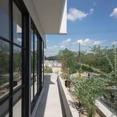 駐車場のある住宅: CO2WORKSが手掛けたベランダです。