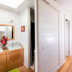 Uma casa de férias para viver todo o ano: Casas de banho  por Rusticasa,Tropical Madeira Acabamento em madeira