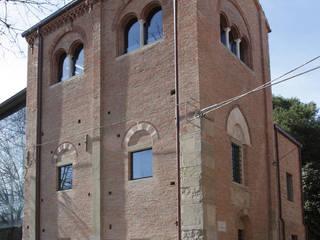 Vista angolare da Piazza Malatesta del campanile dell'ex Cattedrale di Santa Colomba.: Case in stile in stile Moderno di Cumo Mori Roversi Architetti