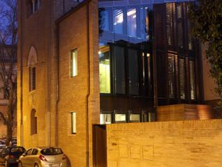Vista di scorcio del complesso da via di Duccio: in primo piano il nuovo volume costruito sul sedime della sagrestia.: Case in stile in stile Moderno di Cumo Mori Roversi Architetti