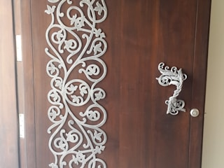 white metal applique on the main door :  Corridor, hallway & stairs  by Hasta architects