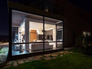 Vista notturna del salone: Case in stile in stile Moderno di Studio 4e