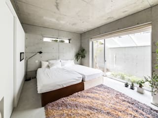 The House supplies a monotonous street with a passing view: Kenji Yanagawa Architect and Associatesが手掛けた寝室です。