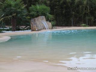 Paisajismo en un jardín con una piscina de arena.: Piscinas de estilo mediterráneo de Ideas Interiorismo Exclusivo, SLU