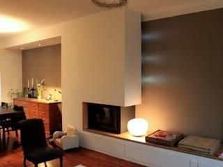 Meuble Cheminée vu depuis le séjour. Un espace multifonction proposant une cheminée, un banc intégrant des rangements, un traitement de l'espace TV / Hifi et une mise en lumière.: Salon de style  par 3B Architecture
