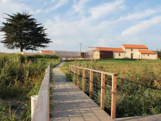 Cheminement depuis les villas pontons vers la cour de la ferme où se situent les équipements collectifs: Hôtels de style  par TICA