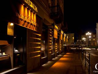 Illuminazione ambrata delle vetrine e del bugnato: Negozi & Locali commerciali in stile  di OperaeLab S.R.L.
