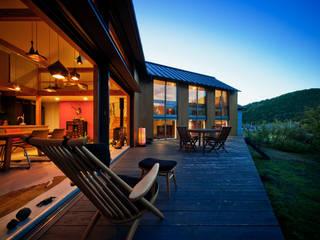 夕景、山に日が沈み内部の色壁や照明が暖かく浮かびあがる: UZUが手掛けた家です。,北欧