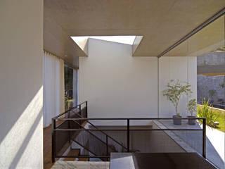 Vista interna mostrando a escada com iluminação zenital.: Corredores e halls de entrada  por Humberto Hermeto