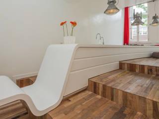 Strak wit Corian en oud grof hergebruikt hout:  Keuken door CUBE architecten