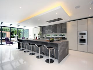 The new kitchen/breakfast bar with dark marble worktops and cabinet doors: modern Kitchen by Hale Brown Architects Ltd