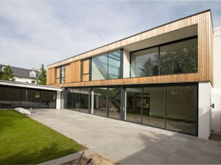 The rear elevation with large glazed windows and balconies: modern Houses by Hale Brown Architects Ltd
