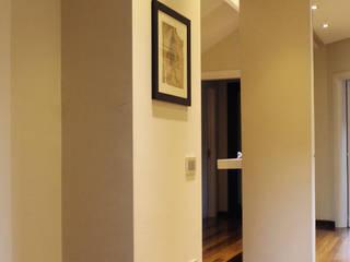 Il disimpegno tra le camere da letto, il grande specchio aumenta la profondità dello spazio.: Ingresso & Corridoio in stile  di Studio Architettura Pappadia