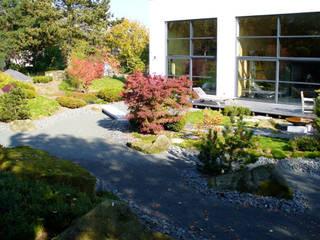 Der Garten ist durch die großen Fenster der Wohnhalle voll einsehbar.:  Garten von ROJI Japanische Gärten