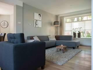 Bank en fauteuil met prachtige lamp en kleine maar sfeervolle salontafel:  Woonkamer door Hemels Wonen interieuradvies en ontwerp