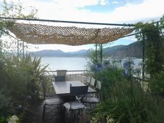 zona pranzo con rete ombreggiante aperta:  in stile  di GARDENStudio 'il giardiniere goloso'
