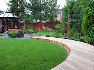 A curved deck links the seating area to the house: asian Garden by Lush Garden Design