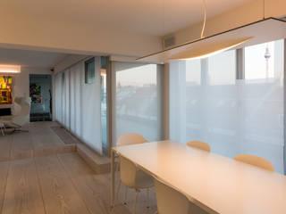 Filter vor den Fenstertüren rahmen den Blick, fokusieren ihn auf herausragende Elemente der Skyline: moderne Esszimmer von Goderbauer Architects