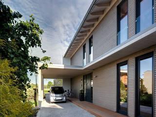 Carport mit Stromtankstelle - mit dem zuviel erzeugten Strom kann hier das E-Mobil betankt werden.: moderne Häuser von Sonnleitner Holzbauwerke GmbH & Co. KG