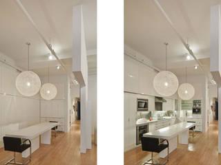 Küchenbereich geöffnet und geschlossen; mit Blick in den Gang, der zu den Nebenräumen führt: moderne Küche von Goderbauer Architects