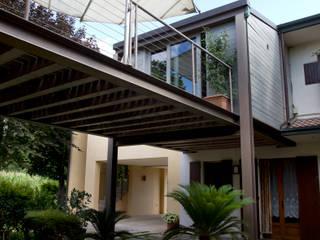 Ampliamento di costruzione di civile abitazione, ristrutturazione di dipendenze rurali, realizzazione di portico e verande: Terrazza in stile  di Studio Negri & Fauro Architetti Associati