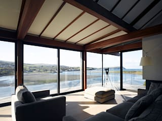 Living room looking out to sea:   by John Pardey Architects