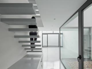 Pasillos y hall de entrada de estilo  por OKULTUS