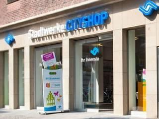 Stadtwerke City Shop | Fassadengestaltung | Natursteinplatten | bockhaus-odenthal architekten:  Geschäftsräume & Stores von bockhaus-odenthal architekten