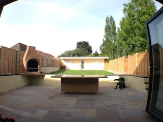 patio with raised sitting area and suspended brick barbecue Progressive Design London Сад