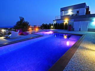 Foto de la piscina comunitaria de noche con la iluminación LED de colores.: Piscinas de estilo moderno de Mellini Internacional, S.L.