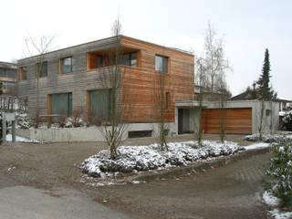 Ansicht Wohnhaus aus Süden - Zufahrt, Garage und Eingangsbereich vor dem höher liegendem Gartenbereich: moderne Häuser von  Architekturbüro André Schär Dipl. Arch. FH