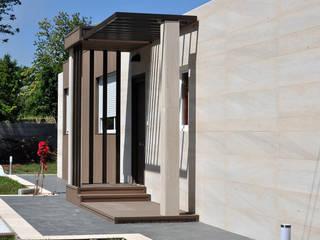 Fachada y porche delanteros en una casa Cube de 100 metros cuadrados Casas estilo moderno: ideas, arquitectura e imágenes de Casas Cube Moderno