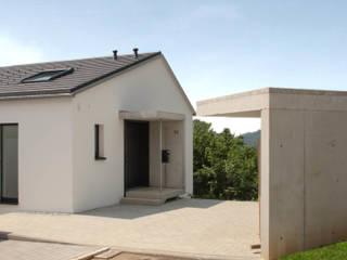Zufahrt mit Carport: minimalistische Häuser von architekturlabor