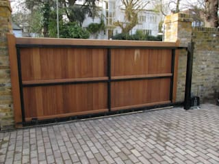 Wooden boarded sliding metal framed gate Mediterranean style garden by Portcullis Electric Gates Mediterranean