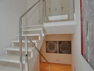 Poliertes Edelstahlgeländer auf weißer Holztreppe:  Flur & Diele von Metallmanufaktur M. van de Weyer