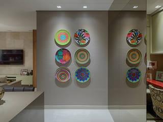 Detalhe pratos decorativos e espelho bronze: Corredores e halls de entrada  por Mariana Borges e Thaysa Godoy,Moderno