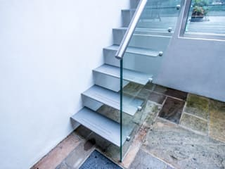 Painted mild steel construction open string-riser access staircase to the rear garden patio with glass balustrades. by Railing London Ltd Сучасний
