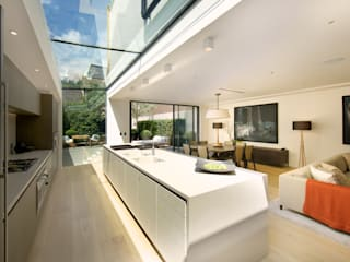 ​Kitchen and sitting area with views of the back garden at Bedford Gardens house. Moderne Küchen von Nash Baker Architects Ltd Modern Glas