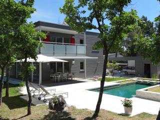 vista de piscina biológica y fachada oeste: Casas de estilo  de Construir con Baufritz