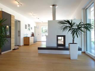 vista interior planta baja, salón con chimenea: Salones de estilo  de Construir con Baufritz