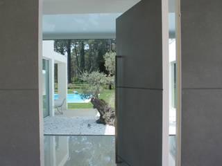 Porta pivotante - Hall de entrada: Corredores e halls de entrada  por Miguel Ferreira Arquitectos