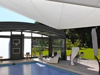 Sonnensegel in elektrisch aufrollbar  über einem Pool: mediterraner Garten von Pina GmbH - Sonnensegel Design