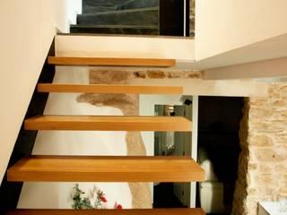 vivienda unifamiliar estilo rustico: Pasillos y vestíbulos de estilo  de cota-zero, tenica y construcción integrada, s.l.