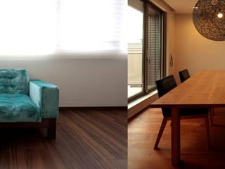 鮮やかなブルーのソファーとブラックチェリーのテーブル: 株式会社 kannaが手掛けたです。