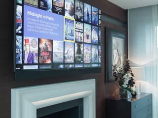 Wall mounted TV on electric bracket モダンデザインの 多目的室 の London Residential AV Solutions Ltd モダン