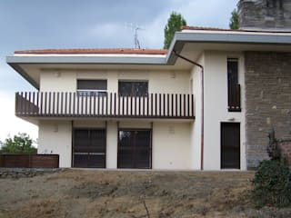 L'ampio balcone con la nuova ringhjera progettata per dare l'immagine moderna ad un edificio già caraterizzato tipologicamente: Terrazza in stile  di Simona Muzzi Architetto