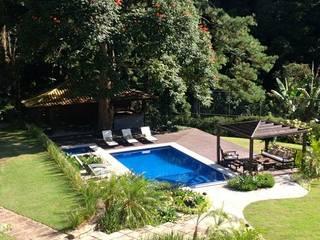 Casa Corrêas Piscinas tropicais por Maria Claudia Faro Tropical