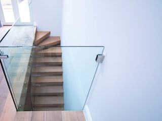 Custom-built cantilever staircase with oak-clad treads and frameless glass balustrades by Railing London Ltd Сучасний