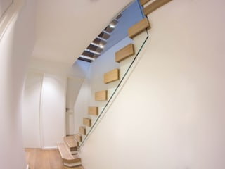 A minimalist floating staircase with oak-clad treads and glass wall balustrades by Railing London Ltd Сучасний